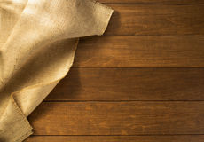 Burlap hessian sacking on wooden. Background royalty free stock image