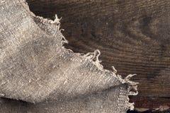 Burlap hessian sacking on wooden background Stock Images
