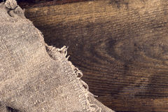 Burlap hessian sacking on wooden background Stock Photos