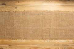 Burlap hessian sacking on wooden background. Burlap hessian sacking on wooden plank board background stock photo