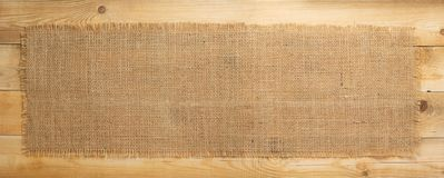 Burlap hessian sacking on wooden background. Burlap hessian sacking on wooden plank board background stock photography