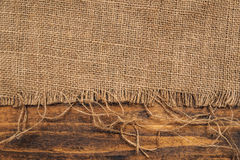 Burlap hessian sacking on wooden background. Rustic backdrop royalty free stock photo