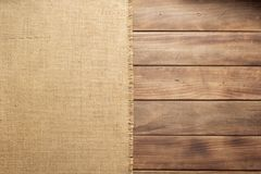 Burlap hessian sacking on wooden background table. Top view royalty free stock photography
