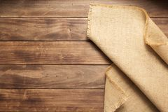 Burlap hessian sacking on wooden background table. Top view stock images