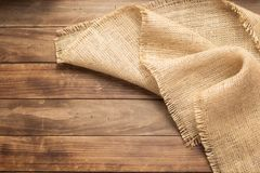 Burlap hessian sacking on wooden background. Table, top view stock photography