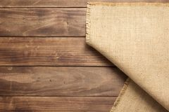 Burlap hessian sacking on wooden background table. Top view stock photo