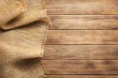 Burlap hessian sacking on wooden background. Table, top view royalty free stock images