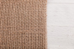Burlap or hessian on white wooden boards Stock Images