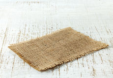 Burlap napkin. On old wooden table royalty free stock photo