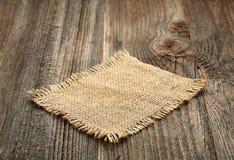 Burlap napkin on wooden table Stock Image