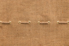 Burlap with one lines of rope and gold rings Stock Images