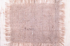 Burlap patch  on wooden background Royalty Free Stock Image