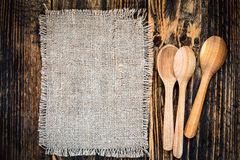 Burlap and rural kitchen utensils on wooden table  view from top. Burlap and rural kitchen utensils on vintage wooden table  view from top. Rustic background Stock Images