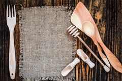 Burlap and rural kitchen utensils on wooden table  view from top. Burlap and rural kitchen utensils on vintage wooden table  view from top. Rustic background Royalty Free Stock Photos