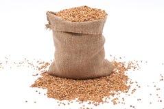 Burlap sack with buckwheat spilling Royalty Free Stock Photos
