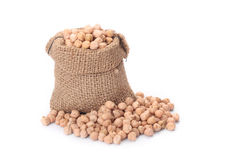 Burlap sack with chickpeas spilling out over a whi Royalty Free Stock Photography