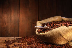 Burlap sack of coffee beans against dark wood