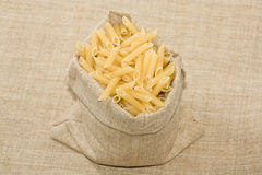 Burlap sack  full with raw  macaroni Stock Image