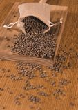 Burlap sack with lentils spilling out over a wooden table Stock Photography