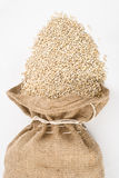 Burlap sack with pearl barley spilling out over a Royalty Free Stock Image