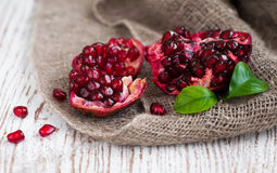 Burlap sack with pomegranate. Burlap sack with Open pomegranate on wooden background royalty free stock photos