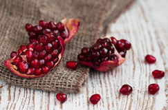 Burlap sack with pomegranate. Burlap sack with Open pomegranate on wooden background royalty free stock photography
