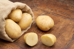 Burlap sack with raw potatoes. And sliced potatoes Stock Images