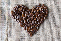 Burlap texture with coffee beans heart shape Royalty Free Stock Photos
