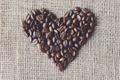 Burlap texture with coffee beans heart shape Royalty Free Stock Photo
