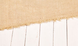 Burlap on a white board. Burlap on white wooden board Royalty Free Stock Photo