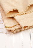 Burlap on a white board. Burlap on white wooden board Royalty Free Stock Photos