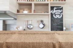 Burlap on wood table top with blur kitchen background. Empty wooden table for product display Stock Photos