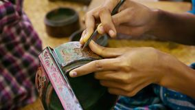 Burma. Artist makes pattern on the product in the workshop stock video footage
