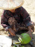 Burma. Fresh Coconut. Lady at Ngapali Beach removing top of coconut to allow access to the milk royalty free stock photography