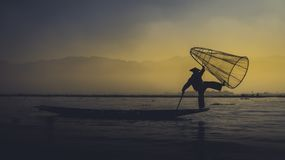 Burma`s Balancing fishermen. Beautiful pictures show how lake people stand on one leg so they can paddle with the other as they hunt carp Royalty Free Stock Image