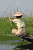 Burman woman on Inle Lake. A woman paddles her boat along Inle Lake in Burma (Myanmar), where people live, farm etc on the lake itself and through small canals royalty free stock photos