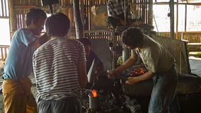 Burmese blacksmiths work in the forge. Manufacture of weapons - traditional way. Stock Photography