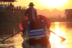 Burmese boatman and buddhist novice sitting in boat Royalty Free Stock Images
