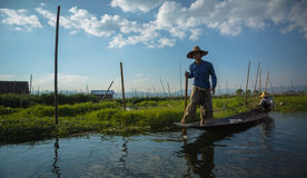 Burmese boatman guides a wooden boat Stock Photography