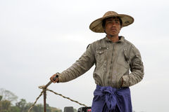 Burmese Boatman. A Burmese man wearing a traditional bamboo hat and skirt drives a motorboat on the Irrawaddy River in Myanmar Stock Photography