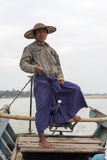 Burmese Boatman. A Burmese man wearing a traditional bamboo hat and skirt drives a motorboat on the Irrawaddy River in Myanmar Stock Image