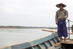 Burmese Boatman. A Burmese man wearing a traditional bamboo hat and skirt drives a motorboat on the Irrawaddy River in Myanmar Stock Photo
