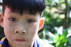 Burmese boy wearing thanaka. A Burmese boy protects his face from the harsh effects of the sun by slathering on some thanaka. Thanaka is a paste made from ground Stock Images