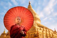 Burmese Buddhist monk walk with umbella in Shwezigon Paya golden pagoda stock photos