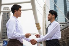Burmese businessmen agree project in city. Two Handsome Burmese or Myanmar businessmen with longyi traditional dress agree or deal project by shake hands with US stock photography