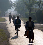 Burmese cycling to work & school. Cycling to work & school in early morning haze. Inle Lake area, Myanmar (Burma royalty free stock images