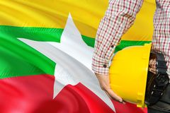 Burmese Engineer is holding yellow safety helmet with waving Myanmar flag background. Construction and building concept.  royalty free stock photos