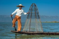 Burmese fisherman on bamboo boat catching fish. Myanmar. Burmese fisherman on bamboo boat catching fish in traditional way with handmade net. Inle lake, Myanmar royalty free stock photos