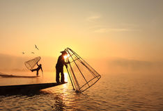 Burmese fisherman on bamboo boat catching fish in traditional wa Stock Photography