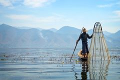Burmese fisherman on bamboo boat catching fish in traditional way with handmade net. Inle lake, Myanmar Burma Stock Photos